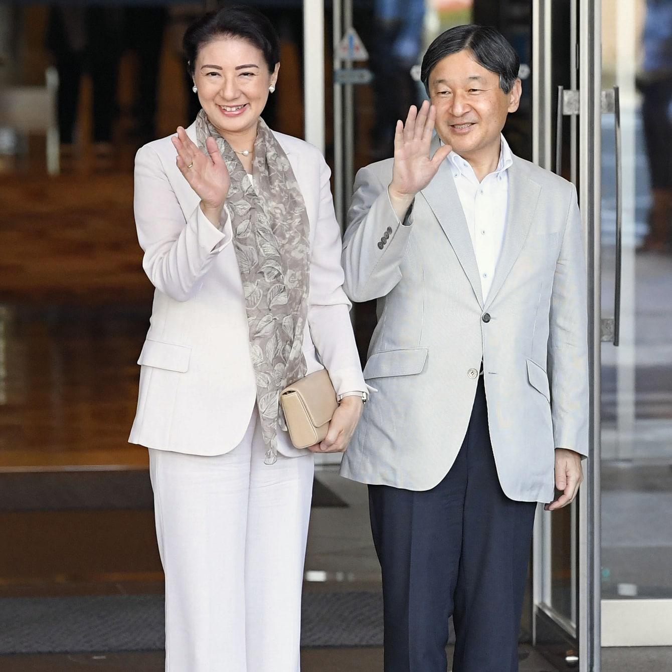すっきりとした白のパンツスーツはシフォンのスカーフで優しい印象に